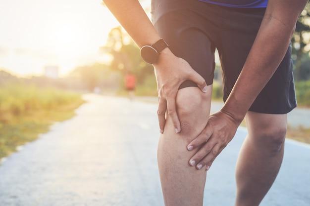Aziatische man houdt op zijn knie tijdens het hardlopen op weg in het park
