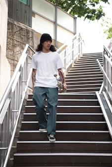 Aziatische man houdt zijn skateboard vast terwijl hij op de trap loopt