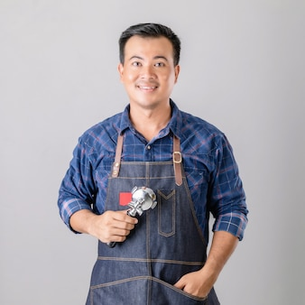 Aziatische man in barista uniform bedrijf koffiemachine gereedschap
