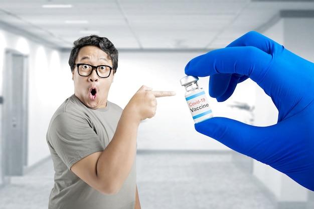 Aziatische man in bril wijzend naar de hand van de gezondheidswerker met handschoenen met covid 19-vaccins voor vaccinatie