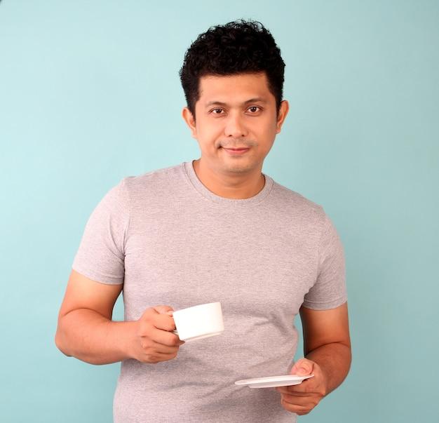 Aziatische man in grijs t-shirt drinkt een kopje koffie, thee op een blauwe.