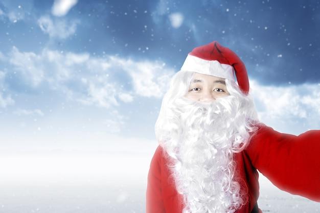 Aziatische man in kerstman kostuum een selfie met een sneeuwval. vrolijk kerstfeest