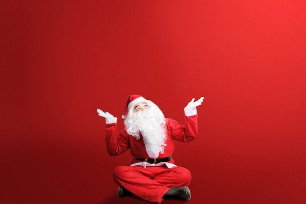 Aziatische man in kerstman kostuum met open palm gebaar zitten met een gekleurde.