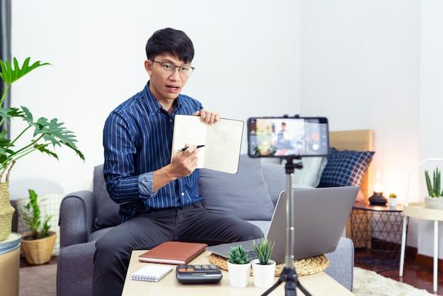 Aziatische man in koptelefoon schrijven van notities in notitieblok kijken naar webinar video cursusstudies via laptop thuis hoorcollege studie online, e-learning concept.
