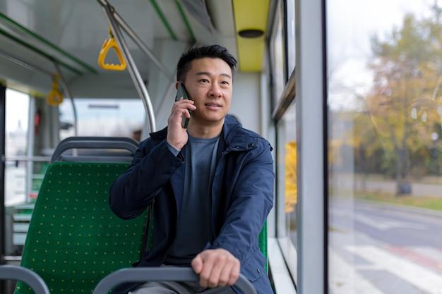 Aziatische man in openbare buspassagier die plezier heeft met praten op mobiele telefoon, in vrijetijdskleding