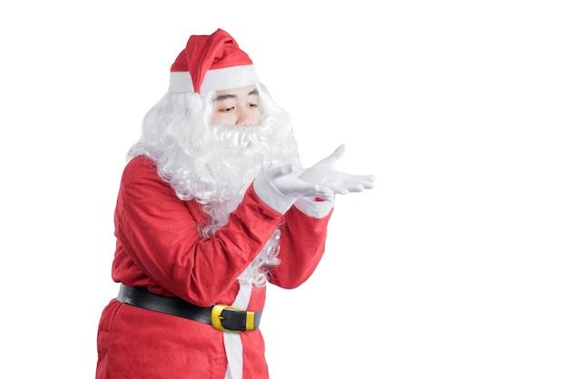 Aziatische man in santa kostuum blaast iets op zijn hand geïsoleerd op witte achtergrond