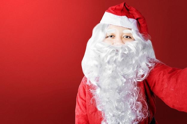 Aziatische man in santa kostuum een selfie met een rode achtergrond. vrolijk kerstfeest