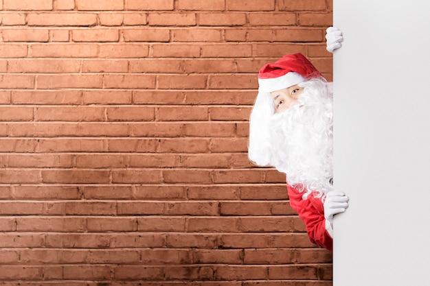 Aziatische man in santa kostuum met een leeg bord met een bakstenen muur.