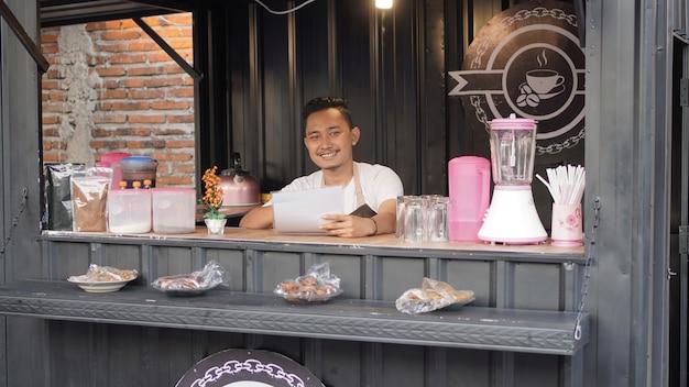 Aziatische man in schort die container angkringan bewaakt met menulijst
