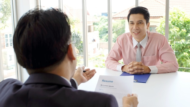 Aziatische man in sollicitatiegesprek op kantoor achtergrond
