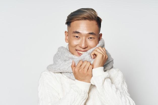 Aziatische man in warme winterkleren poseren in de studio op een gekleurde ondergrond