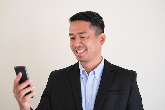 Aziatische man in zwart pak glimlachend gelukkig terwijl hij naar zijn mobiele telefoon kijkt