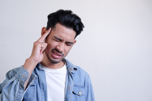 Aziatische man is hoofdpijn, voelt zich ziek met een pijnlijk gezicht en raakt zijn hoofd in het wit