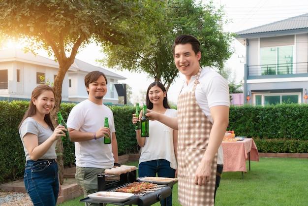 Aziatische man koken barbecue grill en worst voor een groep vrienden om te eten partij in de tuin thuis.