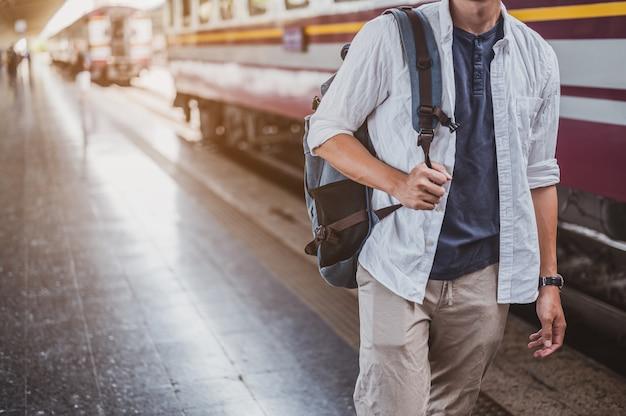 Aziatische man loopt op een trein op een treinstation voor een vakantie. reisconcept. man reiziger toerist wandelen op treinstation.