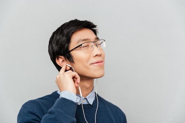 Aziatische man luisteren naar muziek op koptelefoon.