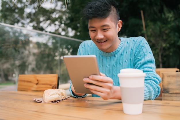 Aziatische man met behulp van zijn digitale tablet.
