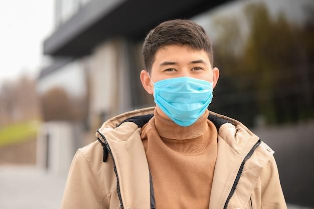 Aziatische man met een beschermend masker op straat in de stad. concept van epidemie