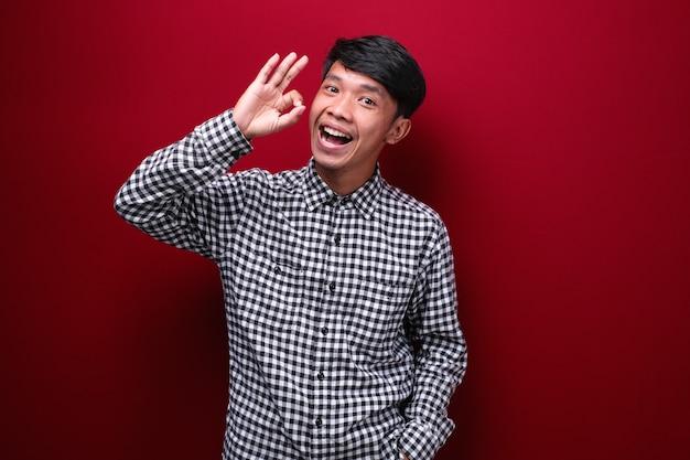 Aziatische man met een geruit hemd met een heerlijke uitdrukking