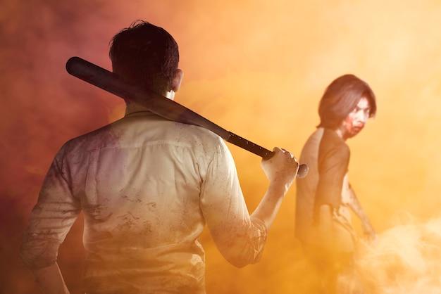Aziatische man met een honkbalknuppel in zijn hand klaar om zombies aan te vallen met een dramatische achtergrond