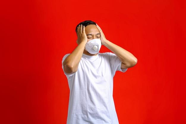 Aziatische man met een medisch masker die er duizelig uitziet terwijl hij zijn ogen sluit en zijn hoofd vasthoudt