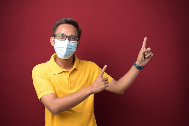 Aziatische man met een medisch masker die iets aan zijn kant presenteert met kopieerruimte op rode achtergrond