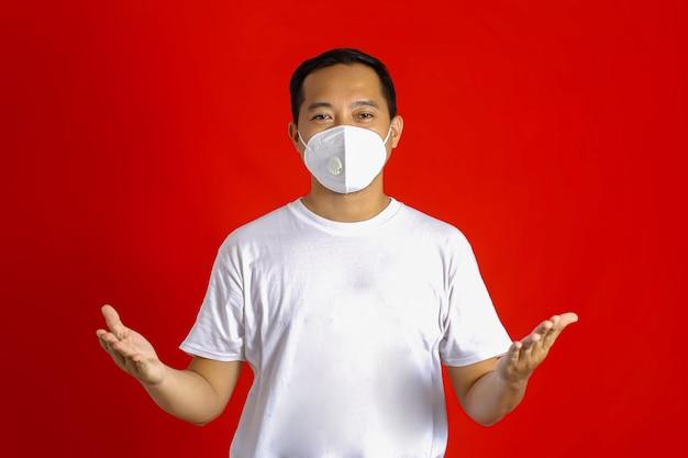 Aziatische man met een medisch masker die naar de camera kijkt met een verwelkomende uitdrukking op een rode achtergrond