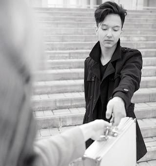 Aziatische man met een metalen koffer in de stad. aziatische en zilveren kast. aziaat met een koffer voor moordenaar. rechercheur met de goederen in de koffer.