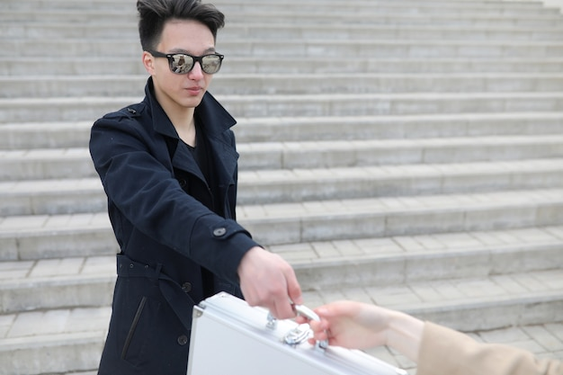 Aziatische man met een metalen koffer in de stad. aziatische en zilveren kast. aziaat met een koffer voor steekpenningen. diller met de goederen in de koffer. bandieten deal.