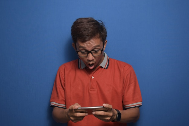 Aziatische man met een oranje casual t-shirt die mobiel spel speelt op zijn smartphone met een verbaasd gezicht