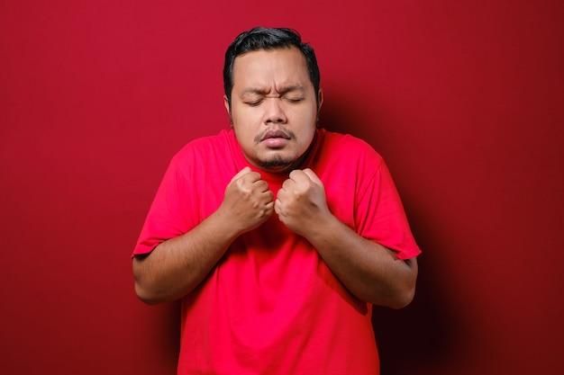 Aziatische man met een rood t-shirt voelt zich onwel, heeft koorts en kijkt rillend over een rode achtergrond