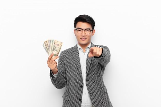 Aziatische man met een tevreden, zelfverzekerde, vriendelijke glimlach, die jou kiest