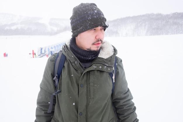 Aziatische man met een trui jas staat in een ski-oord. midden op de sneeuwberg