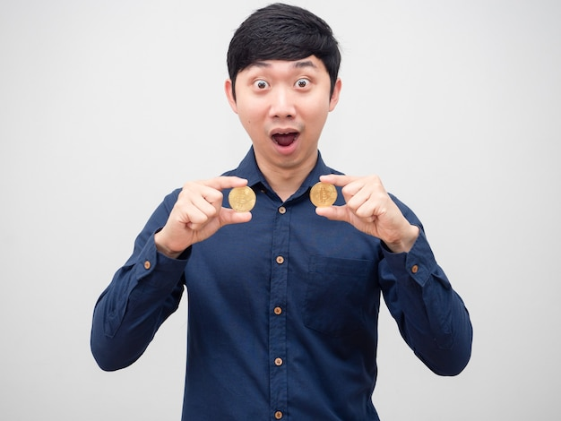 Aziatische man met gouden bitcoin met verbaasd gezicht op witte achtergrond