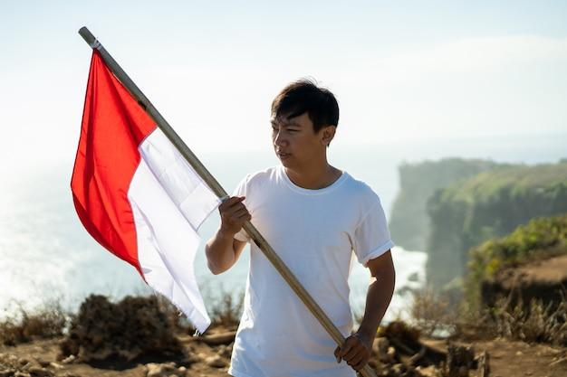 Aziatische man met indonesische vlag van indonesië bovenop de berg