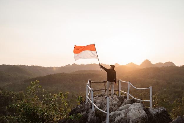 Aziatische man met indonesische vlag vieren onafhankelijkheidsdag