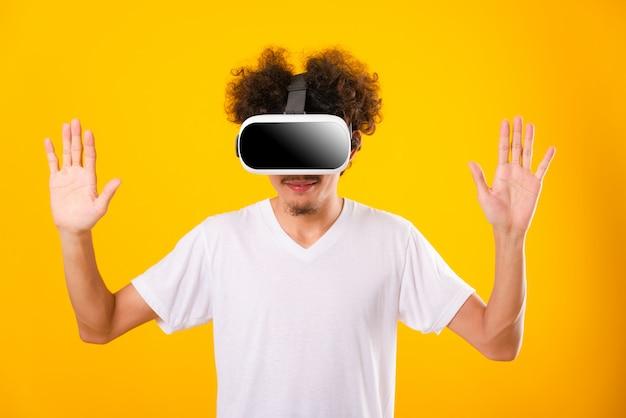 Aziatische man met krullend haar hij met behulp van virtual reality headset