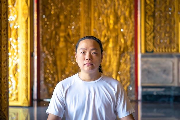 Aziatische man met lang haar ontspant meditatie met een geheel wit kostuum, zittend voor het gouden behang van buddist in de tempel, thailand.