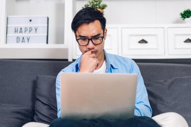 Aziatische man met laptop thuis