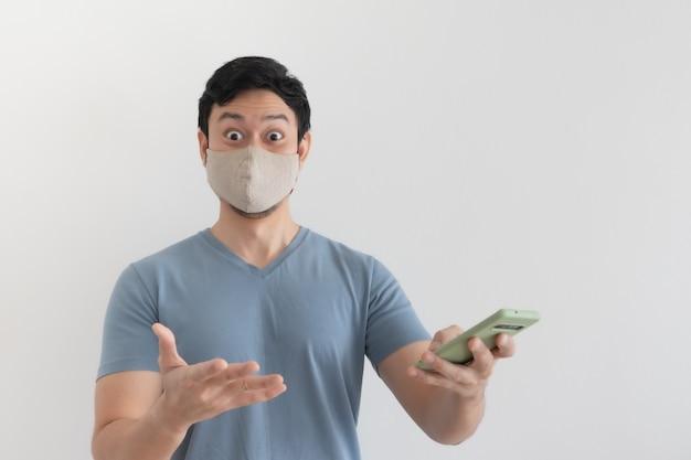 Aziatische man met masker is blij met de promotie in de smartphoneapplicatie
