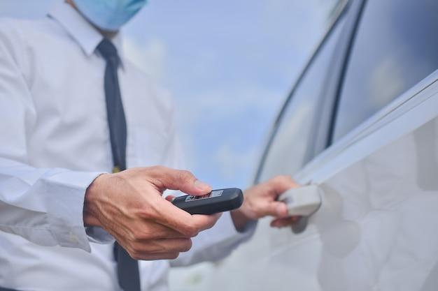Aziatische man met medisch masker en sleutel ingedrukt om de autodeur te openen