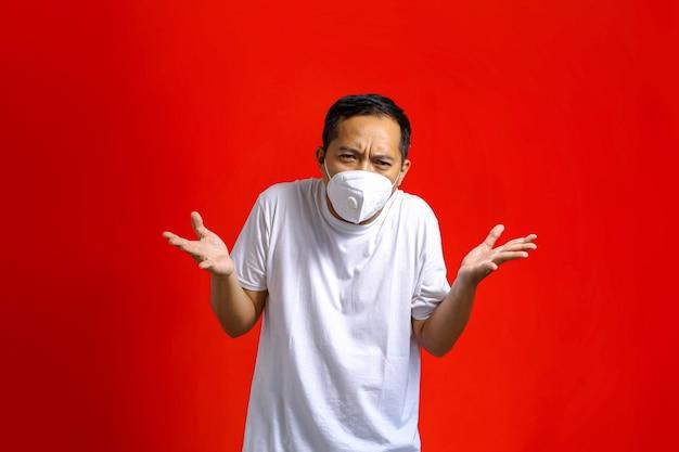 Aziatische man met medisch masker met verwarde uitdrukking op rode achtergrond