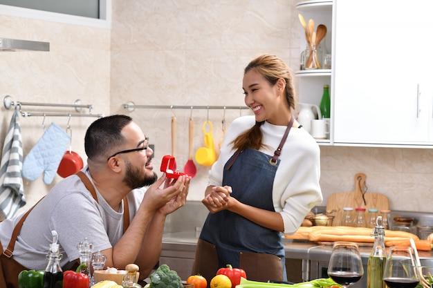 Aziatische man met rode doos met ring voorstellen aan zijn vriendin in de keuken Premium Foto