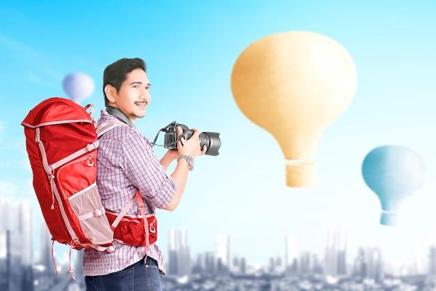 Aziatische man met rugzak en camera kijken naar kleurrijke luchtballon vliegen met stadsgezicht achtergrond