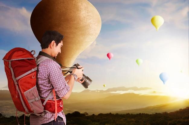 Aziatische man met rugzak en camera kijken naar kleurrijke luchtballon vliegen met zonsondergang hemelachtergrond