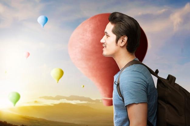 Aziatische man met rugzak kijken naar kleurrijke luchtballon vliegen met dramatische hemelachtergrond