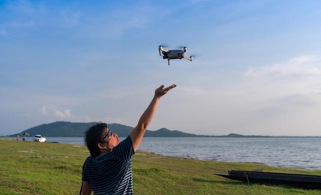 Aziatische man met stoffen beschermend gezichtsmasker opstijgen vliegende drone uit handpalm omhoog in blauwe lucht op groen grasveld in de buurt van meer in heldere dag, man landing drone bij de hand, reizen vakantie ontspannen hobby