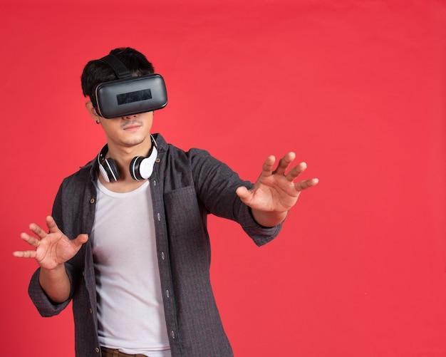 Aziatische man met virtuele hoofdtelefoon op rode muur