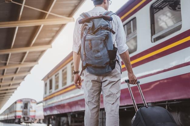 Aziatische man met zijn bagage in het treinstation. reisconcept. man reiziger toerist wandelen op treinstation.