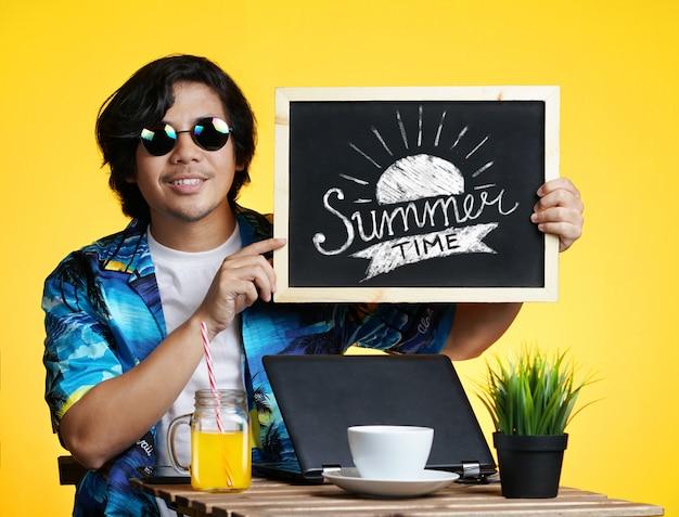 Aziatische man met zomertijd typografie op blackboard tijdens het werken aan zomervakantie